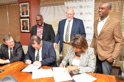 JAMPRO and Benchmark Renewable Energy LLC cement their partnership as Benchmark looks to develop a large-scale bio-ethanol plant in Jamaica.  Diane Edwards, JAMPRO President (seated right) and Juan Briceno,  Business Development Director of Benchmark Renewable Energy LLC (seated centre) sign a Memorandum of Understanding (MOU). Executives from JAMPRO, Capital Solutions and Holesigner Farms look on.